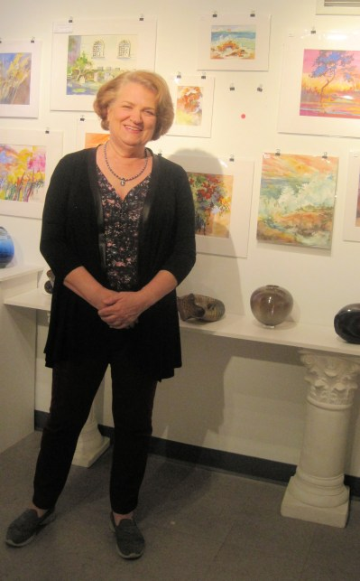 Susan Klas Wright posing near her beautiful landscape paintings.